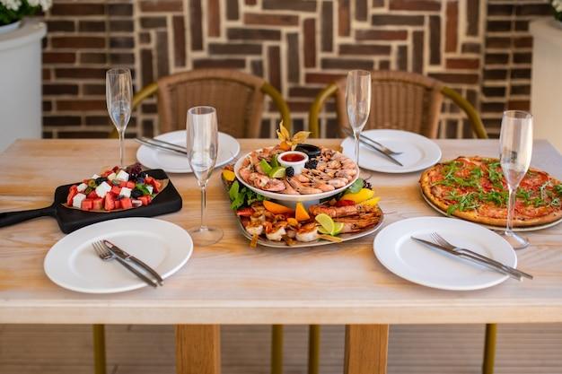 Luksusowy stół w restauracji na stole jest talerz z owocami morza pizza warzywna
