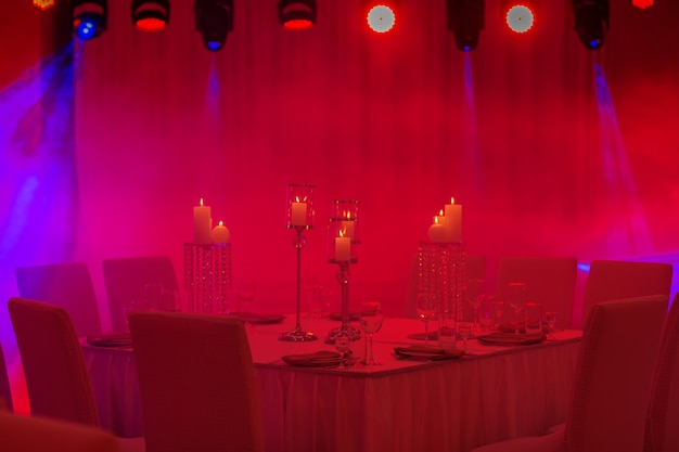 Luksusowy stół weselny z wystrojem, ze srebrnymi świecznikami, świecami i kwiatami w niebieskim świetle. zdjęcie selektywne