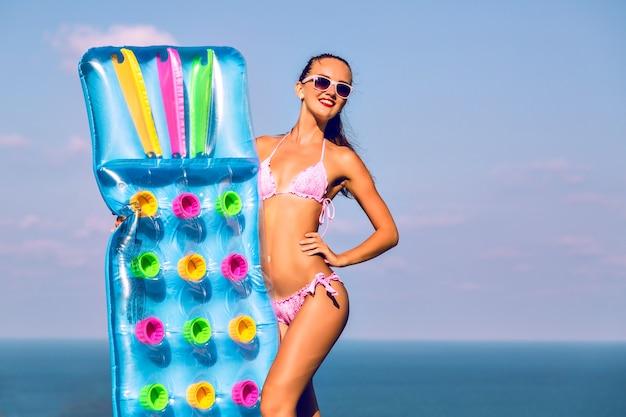Luksusowy styl życia, letni portret szczęśliwej młodej kobiety o opalonym, szczupłym ciele, o słońcu w luksusowej willi, trzymając dmuchane materace na rękach.