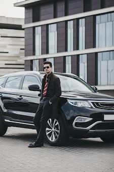 Luksusowy styl życia. przystojny młody człowiek w biznesie nosić stojący w pobliżu jego samochodu
