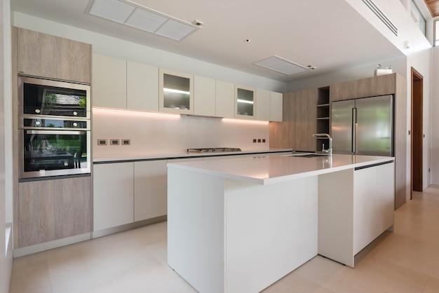 Luksusowy wystrój wnętrz w części kuchennej z licznikiem wyspowym i wbudowanymi meblami