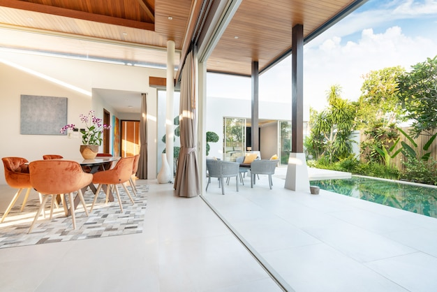 Luksusowy wystrój wnętrz w salonie willi basenowych. przestronna i jasna przestrzeń oraz drewniany stół jadalny