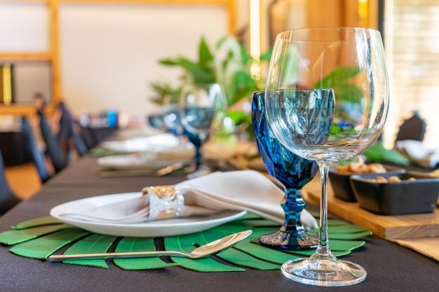 Luksusowy zestaw obiadowy lub kolacyjny na długim stole z czarną nakryciem stołu z dekoracją kwiatową.