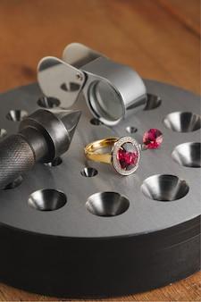 Luksusowy złoty pierścionek z rodolitem i blokami bezela na antycznym pulpicie jubilera.