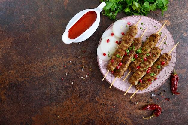 Lula kebab to tradycyjne danie arabskie. szaszłyk mięsny na drewnianych szaszłykach z sosem pomidorowym. widok z góry