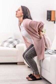 Lumbago, czyli ból krzyża, nagle uderza w kobietę próbującą wstać z kanapy.