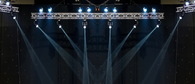 Luminous promienie od koncertowego oświetlenia przeciw ciemnemu tłu, instrumentu muzycznego pojęcie