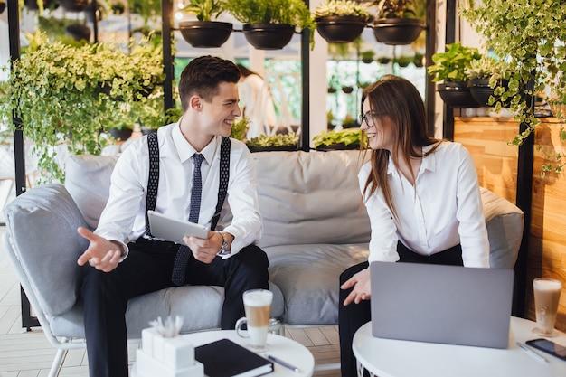 Lunch biznesowy! dwoje młodych ludzi omawia plan dnia w kawiarni z laptopami i tabletem
