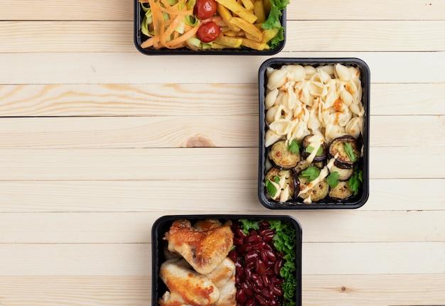 Lunch biznesowy w pudełkach na żywność, pieczone skrzydełka z kurczaka, warzywa na parze, duszone mięso, gotowy posiłek do jedzenia
