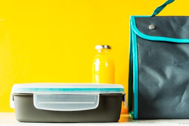 Lunch box z jedzeniem i butelką soku pomarańczowego obok torby na lunch