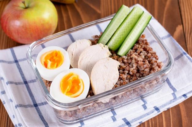 Lunch box z jedzeniem: kasza gryczana, jajko, ogórek. koncepcja zdrowej żywności