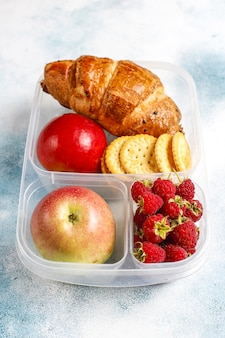 Lunch box ze świeżo upieczonym rogalikiem, krakersami, owocami i malinami.