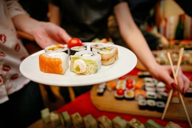 Lunch sushi, sushi na talerzu, ręce z pałeczkami