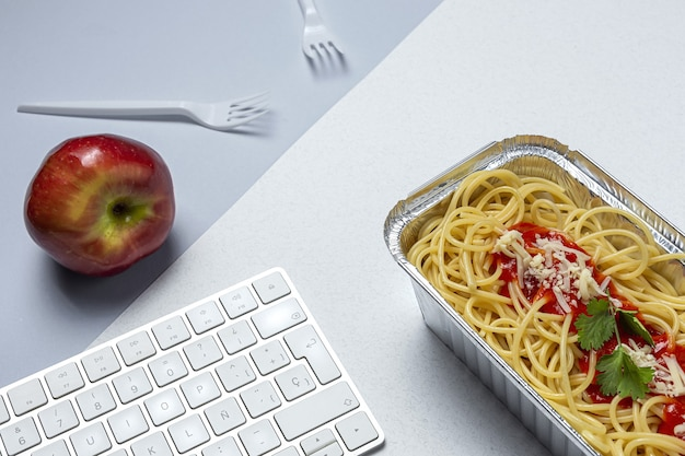 Lunch w miejscu pracy domowe i zdrowe spaghetti z pomidorami i serem na stole roboczym z klawiaturą komputera. jedzenie w domu dla koncepcji biura. jedzenie na wynos