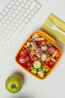 Lunch w miejscu pracy zdrowy makaron z tuńczykiem, pomidorkami koktajlowymi, marchewką, ogórkiem w pudełku na lunch na stole roboczym. jedzenie w domu dla koncepcji biura