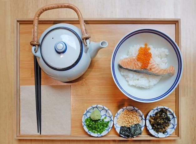 Lunch w stylu japońskim z przystawką, smażony łosoś na ryżu podawany z zupą w garnku.