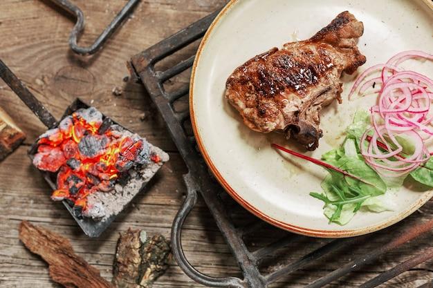 Lunch z grillowanym mięsem wieprzowym na stole vintage w stylu rustykalnym. jedzenie bbc.