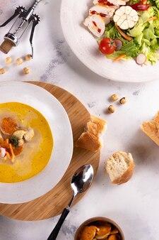 Lunch zupa z kurczaka z grzankami i sałatką z piersi kurczaka i wino na jasnym tle