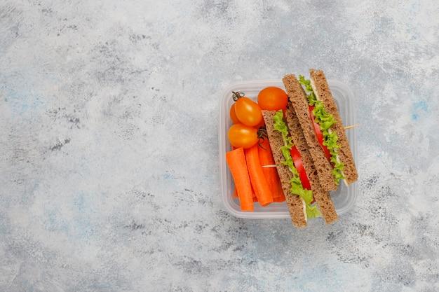Lunchbox z kanapką, warzywami, owocami na bielu.