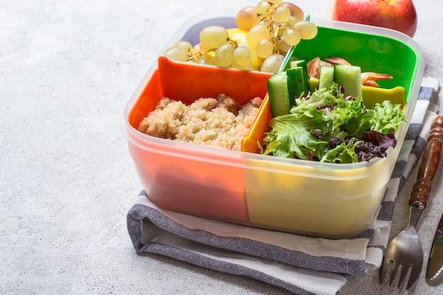 Lunchbox ze zbilansowanym posiłkiem. owoce warzywa białka i węglowodany w kolorowym pudełku. koncepcja zdrowej żywności w biurze