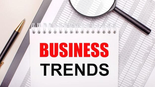 Lupa biurkowa, raporty, długopis i notatnik z tekstem trendy biznesowe. pomysł na biznes