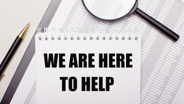 Lupa biurkowa, raporty, długopis i notes z tekstem jesteśmy tutaj pomoc. pomysł na biznes