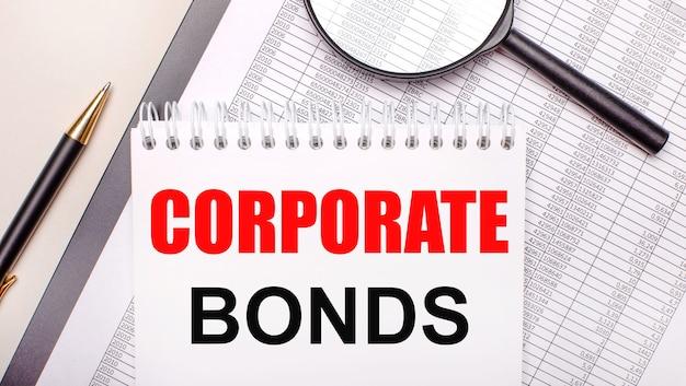 Lupa biurkowa, raporty, długopis i notes z tekstem obligacje korporacyjne. pomysł na biznes