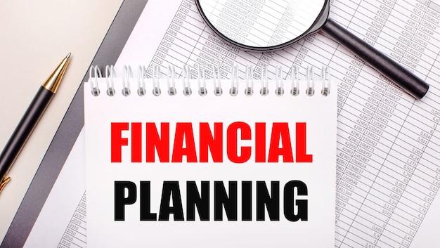 Lupa biurkowa, raporty, długopis i notes z tekstem planowanie finansowe. pomysł na biznes