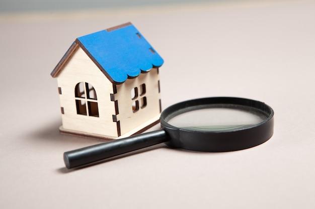 Lupa i dom na różowym tle. koncepcja wyszukiwania w domu