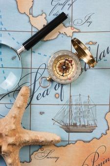 Lupa i kompas na stylizowanej mapie