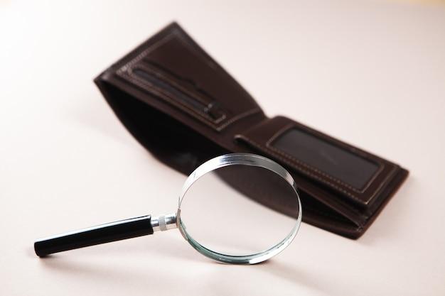 Lupa i pusty portfel na stole