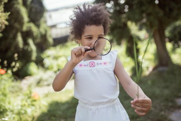 Lupa. mała dziewczynka z kręconymi włosami trzyma lupę i szuka zainteresowania