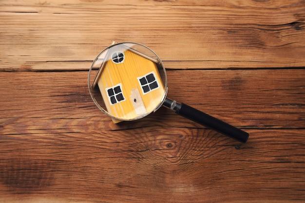 Lupa na drewnianym małym domku na stole