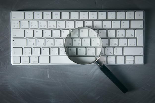 Lupa na klawiaturze komputera na stole