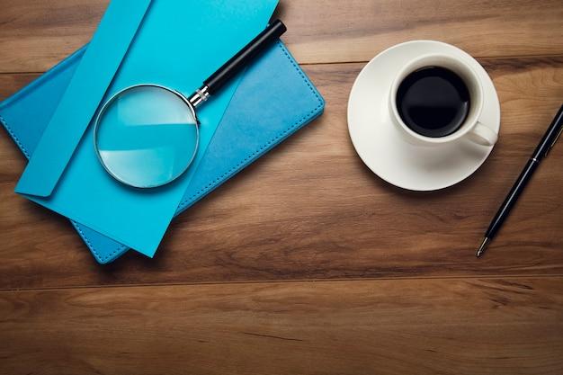 Lupa na liście i filiżankę kawy na stole