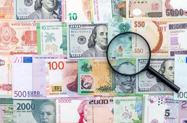 Lupa na międzynarodowych banknotach pieniężnych