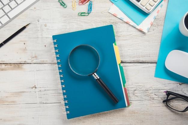 Lupa na notatniku z stacjonarnym z komputerem na stole roboczym