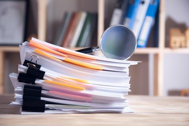 Lupa na zapas papierów na stole roboczym