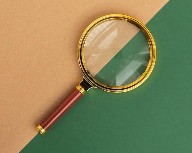 Lupa na zielonym i brązowym tle koncepcji wyszukiwania i badania