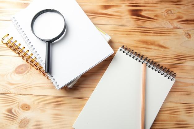 Lupa, notatnik i długopis na drewnianym pulpicie