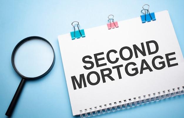Lupa powiększająca ze znakiem second mortgage w notatniku papieru na niebieskim stole.