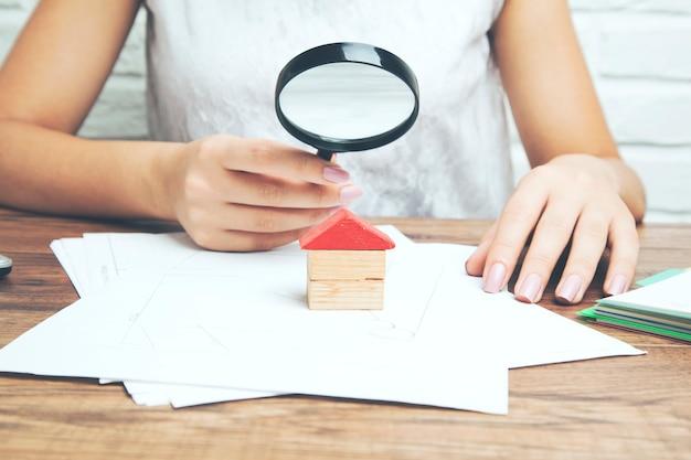 Lupa ręczna bizneswoman i model domu