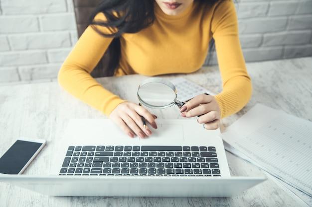 Lupa ręczna kobiety i komputer na stole