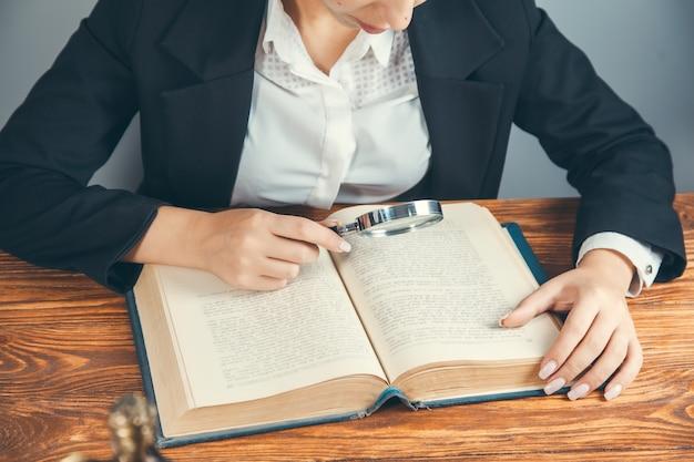 Lupa ręczna kobiety i książka na drewnianym stole