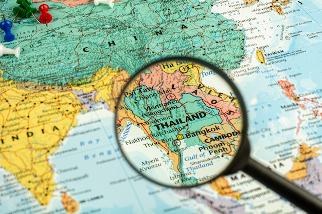 Lupa selektywna na mapie tajlandii. - koncepcja ekonomiczna i podróżnicza.