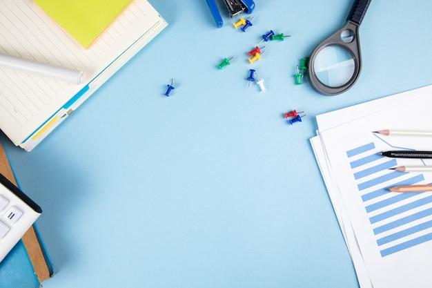 Lupa, statystyki i kalkulator na niebieskim stole