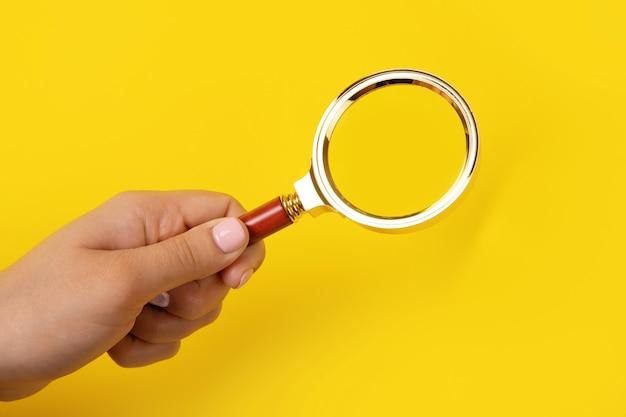 Lupa w ręku na żółtym tle