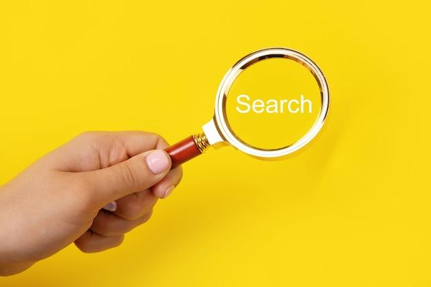 Lupa w ręku z wyszukiwaniem napisem na żółtym tle, koncepcja wyszukiwania