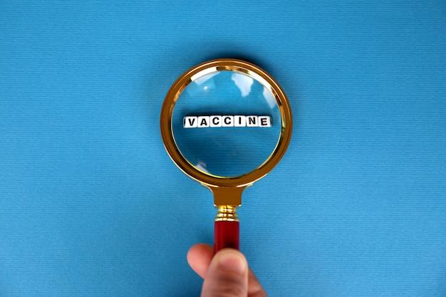 Lupa z napisem szczepionki na niebieskim tle, koncepcja wyszukiwania szczepionki