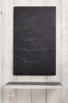 Łupek kamienna drewniana półka o białej ścianie tekstura tło